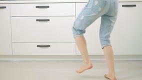Dança engraçada nova alegre da mulher na cozinha em casa vídeos de arquivo