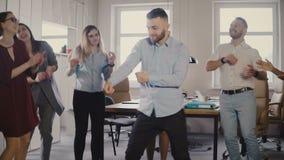 Dança europeia nova do homem de negócios junto com colegas no partido de escritório ocasional do divertimento, comemorando a prom filme