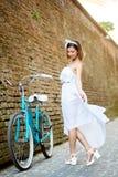 Dança fêmea consideravelmente nova ao lado da bicicleta azul perto da parede de tijolo da cidade imagens de stock