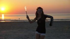 Dança fêmea do adolescente novo no crepúsculo em uma praia com uma vela do fogo de artifício filme