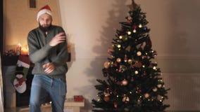 Dança farpada engraçada do homem perto da árvore de Natal O homem considerável feliz no chapéu de Santa move seu corpo na maneira vídeos de arquivo