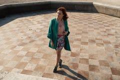 Dança feliz da jovem mulher em uma fonte vazia que veste uma saia colorida fotos de stock royalty free