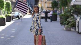 Dança feliz da jovem mulher na rua com sacos de compras Tiro do movimento lento 4K filme