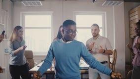 Dança feliz do CEO do afro-americano com os amigos no partido de escritório ocasional Atividade do divertimento da parte dos cole video estoque