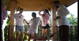 Dança feliz do grupo dos homens e das mulheres exterior no terraço do verão, raça da mistura dos amigos alegre tendo o divertimen filme