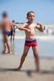 Dança feliz do rapaz pequeno na praia no tempo do dia Foto de Stock Royalty Free