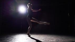 Dança flexível profissional da bailarina em suas sapatas de bailado do pointe no projetor no fundo preto no estúdio ballet filme