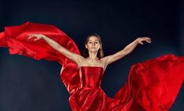 Dança inspirada bonita da mulher em um voo de seda vermelho do vestido imagem de stock