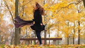 Dança louca da mulher feliz no parque do outono, árvores de bordo coloridas brilhantes filme