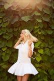 A dança loura da mulher em um verde sae ao escutar a música Imagem de Stock Royalty Free