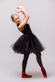 Dança loura nova da menina da bailarina e levantamento em sapatas pretas do tutu e de bailado no fundo cinzento Imagem de Stock