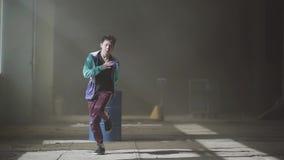 Dança masculina do dançarino do hip-hop asiático novo na construção abandonada escura na frente do tambor de gás azul contemporar filme