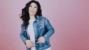 A dança moreno da menina ri em um fundo cor-de-rosa video estoque