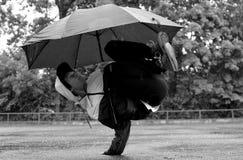 Dança nova do breakdance do indivíduo na chuva com um guarda-chuva fotos de stock royalty free