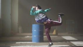 Dança nova do dançarino do hip-hop dos esportes perto do tambor em uma construção abandonada na névoa Cultura de hip-hop rehearsa vídeos de arquivo