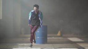 Dança nova hábil do dançarino do hip-hop perto do tambor em uma construção abandonada na névoa Cultura de hip-hop rehearsal video estoque