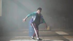 Dança nova profissional do dançarino do hip-hop perto do tambor em uma construção abandonada na névoa Cultura de hip-hop vídeos de arquivo