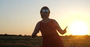 Dança otimista da mulher em um campo enorme no por do sol no verão video estoque