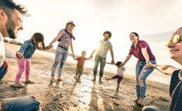 Dança redonda das famílias multirraciais felizes na praia no por do sol foto de stock