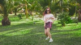 Dança ruivo bonita nova da menina no parque mulher em uma mini dança da saia em um parque tropical em um fundo de vídeos de arquivo