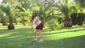 Dança ruivo bonita nova da menina no parque mulher em uma mini dança da saia em um parque tropical em um fundo de video estoque