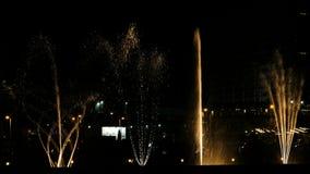 Dançar fontes e espirra da água na noite na cidade Luzes, cores e mostra da noite da música video estoque