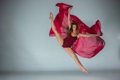 Dançarino bonito novo da mulher no roupa de banho vermelho que levanta em uma luz - fundo cinzento do estúdio imagens de stock