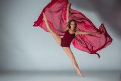Dançarino bonito novo da mulher no roupa de banho vermelho que levanta em uma luz - fundo cinzento do estúdio foto de stock