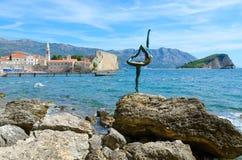Dançarino da bailarina da escultura de Budva no fundo da cidade e da ilha velhas de Sveti Nikola, Budva, Montenegro fotos de stock royalty free