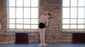Dançarino de bailado fêmea novo que exercita na classe do bailado vídeos de arquivo