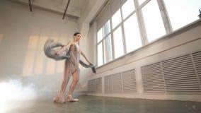 Dançarino de bailado flexível que estica no estúdio iluminado escuro, movimento lento filme