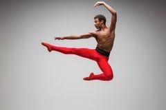 Dançarino de bailado moderno novo e à moda no fundo cinzento Fotos de Stock