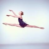 Dançarino de bailado novo bonito que salta em um cinza fotografia de stock
