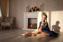 Dançarino de bailado profissional que senta-se no assoalho de madeira Bailarina fêmea que tem um conceito do bailado do resto imagem de stock