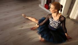 Dançarino de bailado que senta-se no assoalho de madeira Bailarina fêmea que tem um conceito do bailado do resto imagens de stock royalty free