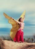 Dançarino de barriga adolescente com as asas que executam na praia Fotografia de Stock