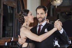 Dançarino de sorriso Performing Gentle Embrace do tango com sócio foto de stock royalty free