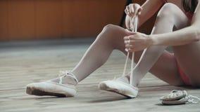 Dançarino do balerina da menina que põe sobre suas sapatas de bailado imagem de stock royalty free