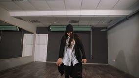 Dançarino fêmea na camisa branca e na calças preta que mostram a dança moderna do hip-hop na sala de aula com os espelhos que olh vídeos de arquivo