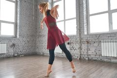 Dançarino fêmea novo que salta e que dança no gym imagens de stock