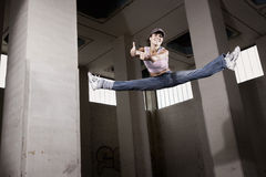 Dançarino fêmea que salta com polegares acima. Fotografia de Stock