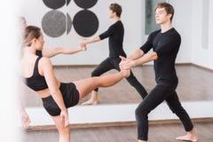 Dançarino masculino bonito que guarda o pé de seu sócio Imagens de Stock