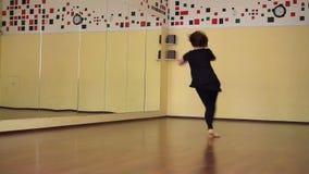 Dançarino moderno que aquece-se em um estúdio com espelhos Dança de formação da menina video estoque