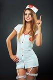 Dançarino novo e bonito no traje da enfermeira que levanta no estúdio Fotos de Stock Royalty Free