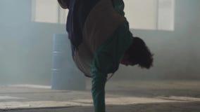 Dançarino novo experiente da rua do hip-hop que executa na frente da grande janela na construção abandonada escura contemporary filme