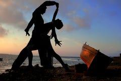 Dançarinos da silhueta ao lado do mar fotos de stock royalty free