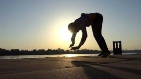 Danças felizes do homem em seus braços em um banco de rio no verão no slo-mo video estoque