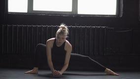 Danças louras flexíveis da moça perto da janela filme