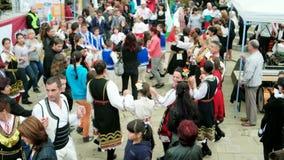 Danças tradicionais búlgaras, dança do grupo de pessoas no círculo, trajes nacionais, eventos do ar livre filme