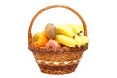 Dan fruto las granadas, plátanos, caquis, kiwi en cesta Imágenes de archivo libres de regalías